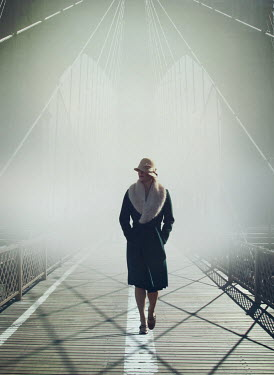 Mark Owen WOMAN IN HAT WALKING ON FOGGY BRIDGE Women