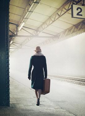 Mark Owen WOMAN CARRYING SUITCASE ON RAILWAY PLATFORM Women