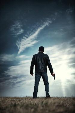 Magdalena Russocka modern man in black leather jacket holding gun outside
