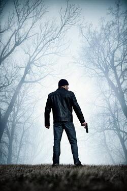 Magdalena Russocka modern man in black leather jacket holding gun in woods