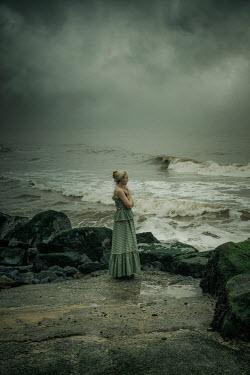 Nic Skerten BLONDE GIRL WATCHING SEA WITH STORMY SKY Women