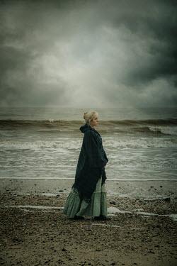Nic Skerten WOMAN IN SHAWL WALKING BY STORMY SEA Women
