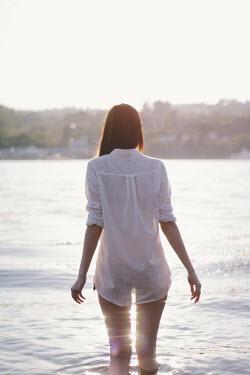 Alina Zhidovinova GIRL STANDING IN SEA IN SUNLIGHT Women