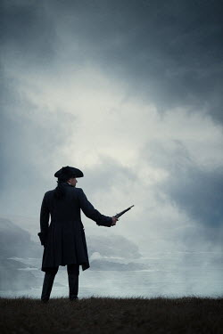 Magdalena Russocka historical man in tricorn hat with flintlock standing by sea