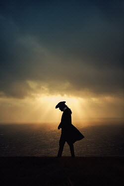 Magdalena Russocka silhouette of historical man in tricorn hat walking by sea at sunset