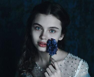Alina Zhidovinova CLOSE UP OF GIRL WITH BLUE FLOWER Children