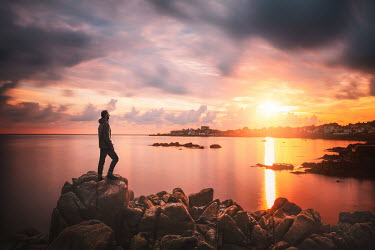 Evelina Kremsdorf MAN ON ROCKS BY SEA WATCHING SUNSET Men