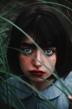 Jovana Rikalo CLOSE UP OF GIRL WITH FRECKLES BEHIND LONG GRASS Women