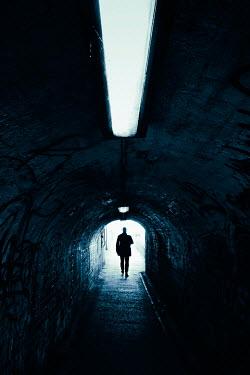 Tim Robinson SILHOUETTED MAN WALKING IN DARK TUNNEL Men