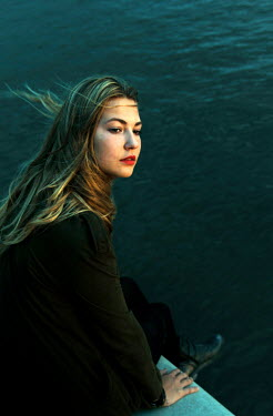 Ute Klaphake BLONDE GIRL SITTING BY WINDY SEA Women