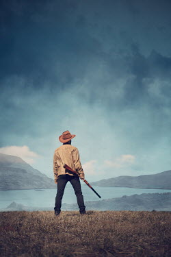 Magdalena Russocka cowboy man with rifle standing by lake with mountains