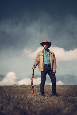 Magdalena Russocka cowboy man with rifle standing in field with mountains