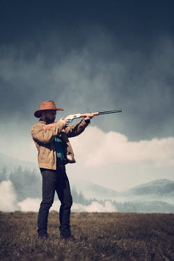 Magdalena Russocka cowboy man aiming with rifle in field with mountains