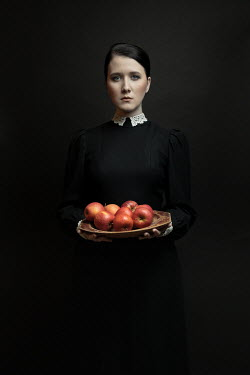 Dorota Gorecka Young woman in black Victorian dress holding tray of apples