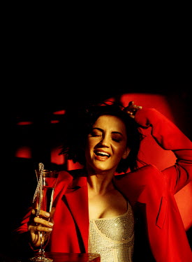 Marta Syrko Young woman in lingerie and red coat holding champagne glass