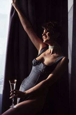 Marta Syrko Smiling young woman in bodice holding champagne glass by window