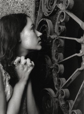 Steven J Gelberg Young woman with clasped hands by wrought iron gate