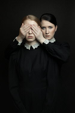 Dorota Gorecka Young woman in black Victorian dress covering another woman's eyes