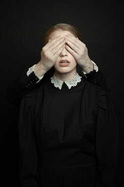 Dorota Gorecka Young woman in Victorian dress with hands covering her eyes