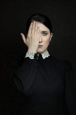 Dorota Gorecka Young woman in black Victorian dress covering her eye