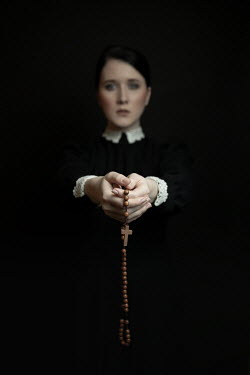 Dorota Gorecka Young woman in black Victorian dress holding rosary beads