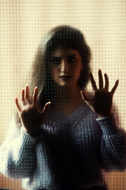 Mohamad Itani Young woman in gray sweater behind window