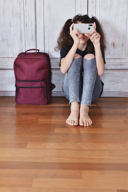 Tanya Gramatikova Teenage girl with smart phone sitting by backpack