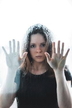 Ildiko Neer Young girl staring behind wet window