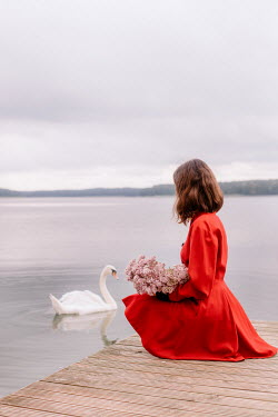 Klaudia Rataj Young woman with bouquet sitting on jetty by swan swimming on lake