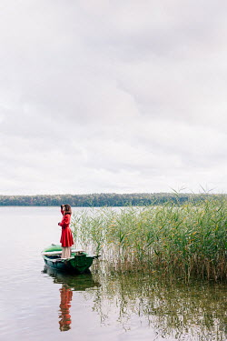 Klaudia Rataj Young woman in red coat standing in dinghy on lake