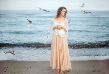 Klaudia Rataj Young woman in white shawl and pink skirt on beach