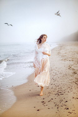 Klaudia Rataj Young woman in white shawl and pink skirt walking on beach