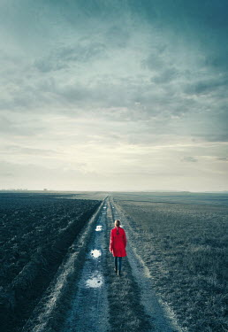 Magdalena Russocka woman in red coat walking on country road