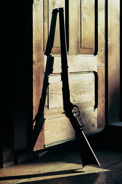 Magdalena Russocka Rifle leaning on wooden door