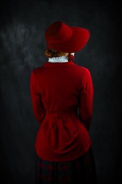Ildiko Neer Historical woman in red coat and bonnet from behind