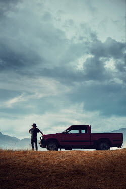 Magdalena Russocka man in cowboy hat standing next to pick-up truck