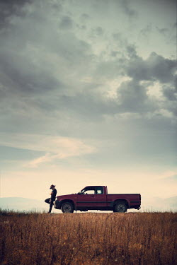 Magdalena Russocka man in cowboy hat leaning against pick-up truck