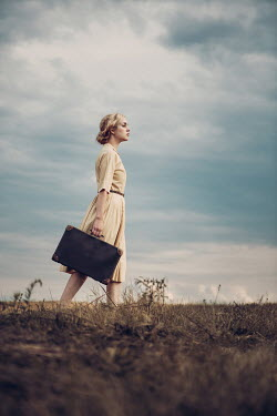 Magdalena Russocka retro woman with suitcase walking in countryside
