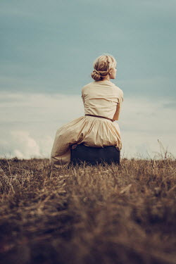 Magdalena Russocka retro woman sitting on suitcase in countryside