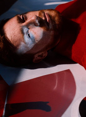 Marta Syrko CLOSE UP OF MAN WITH RED HAIR LYING ON FLOOR Men