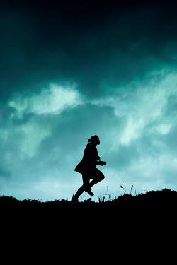 Rekha Garton SILHOUETTED GIRL RUNNING AT DUSK IN COUNTRYSIDE Women