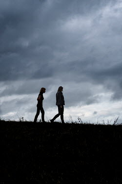 Stephen Mulcahey TWO WOMEN WALKING IN FIELD AT DUSK Women