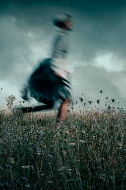 Rekha Garton HISTORICAL GIRL RUNNING IN FIELD WITH STORMY SKY Women
