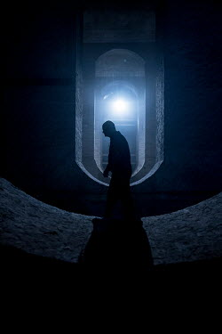 Colin Hutton SILHOUETTED MAN IN LARGE STONE BUILDING AT NIGHT Men