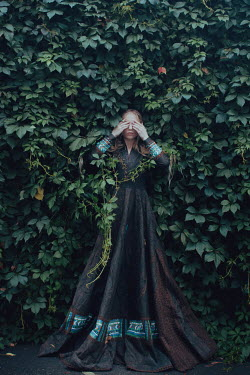 Irina Orwald BLONDE GIRL COVERING EYES BY WALL OF LEAVES Women