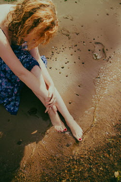 Irina Orwald BAREFOOT WOMAN SITTING ON SANDY BEACH Women