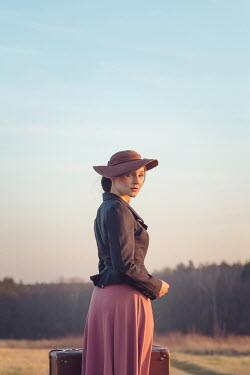 Joanna Czogala WOMAN IN HAT CARRYING SUITCASE IN COUNTRYSIDE Women