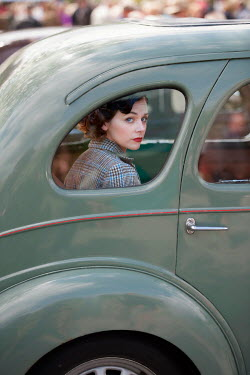 Lee Avison 1940s woman looking out of the window of a vintage car from the back seat
