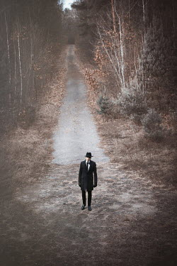 Natasza Fiedotjew Man in black coat and hat standing on walkway in woods
