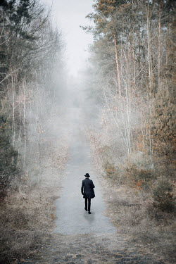 Natasza Fiedotjew Man in black coat and hat walking in woods
